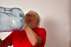 Thirsty old man drinking from a 5 gallon water bottle. Thirst buster, thirsty gentleman drinks from a 5 gallon water bottle.