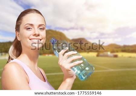Thirsty woman holding a bottle of water and drinks