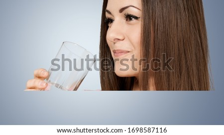 Thirsty woman holding a glass of water and drinks