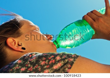 Thirsty woman is drinking fresh water on a sunny day