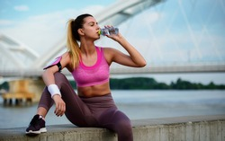 Thirsty woman take a break and drinking water after training outdoor. Fitness, sport, lifestyle concept