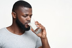 Thirsty young african man holding glass of drinking water for body health, healthy lifestyle, thirst and hydration concept, free space