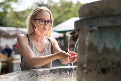 Thirsty young casual cucasian woman wearing medical face mask drinking water from public city fountain on a hot summer day. New life during covid epidemic.