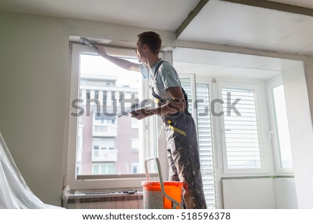 Thirty years old manual worker with wall plastering tools inside a house. Plasterer renovating indoor walls and ceilings with float and plaster.