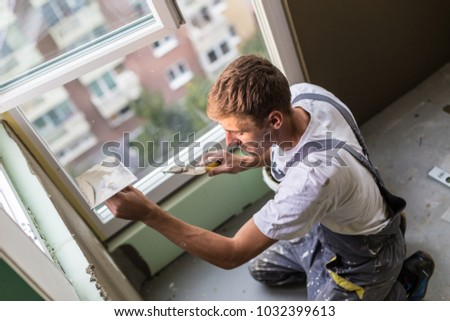 Thirty years old manual worker with wall plastering tools renovating house. Plasterer renovating indoor walls and ceilings with float and plaster.