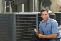 Thirtyish air conditioning repairman with clipboard