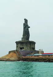 Thiruvalluvar statue on a small rock island during monsoon located at Kanyakumari, India. A shot taken during a ferry ride towards the statue.