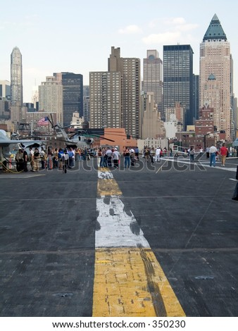 This a view of the New York City skyline from the deck of an aircraft carrier.