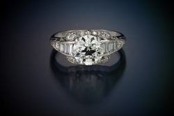 This antique diamond engagement ring with a one plus carat center stone is enhanced by accent side diamonds and set in platinum. Shown laying on a black reflective background.