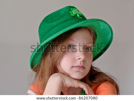 This beautiful green eyed, 9 year old Caucasian girl is wearing a green St. Patrick's Day hat in a closeup on a light background.  Her facial expression is a more serious tone.