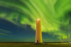 This beautiful northern lights or aurora borealis in Iceland was taken at or around lighthouse near Keflavik during a winter night. Green northern lights. Starry sky with polar lights.