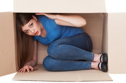 This box is too small. Shocked young woman looking at camera while sitting in a cardboard box
