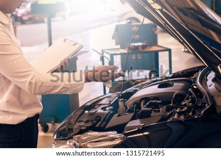 This career man saleman business inspection writing note on notepad or book, paper with car blurry background.for transport automobile automotive Illustrative editorial image #1315721495