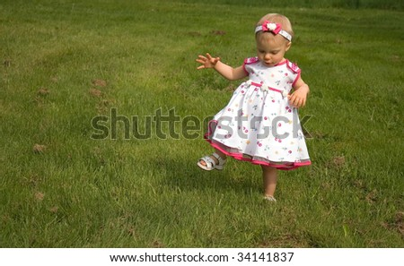 This cute toddler girl is stepping high in the long grass, not liking it touching her legs.