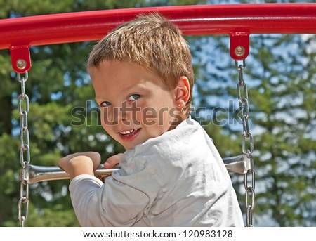 This cute 4 year old Caucasian boy with blue eyes and freckles in playing on some playground equipment outdoors.  He's wearing a long sleeve white t-shirt.