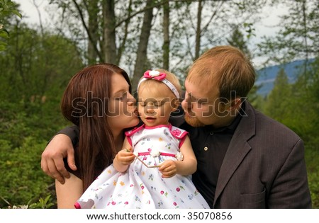 This cute young Caucasian family is outdoors together and mom is kissing baby girl while dad embraces both.