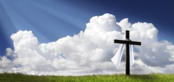 This dramatic Easter Morning Sunrise panorama with blue sky, bright clouds, sunbeams, and large cross on a grass covered hill makes a great banner cover for print or web.