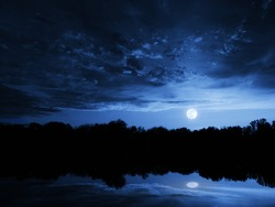 This dramatic moon rise in a deep blue night time sky is accented by highlighted clouds and beautiful, calm lake reflection.