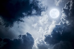 This dramatic photo illustration of a nighttime sky with brightly lit clouds and large, full, Blue Moon would make a great background for many uses.