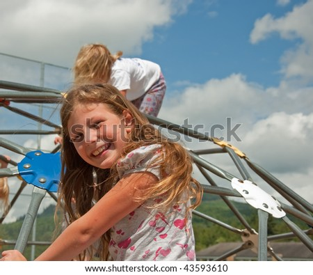 This eight year old Caucasian girl is smiling and happy while playing outdoors on playground equipment on a windy, cloudy day.