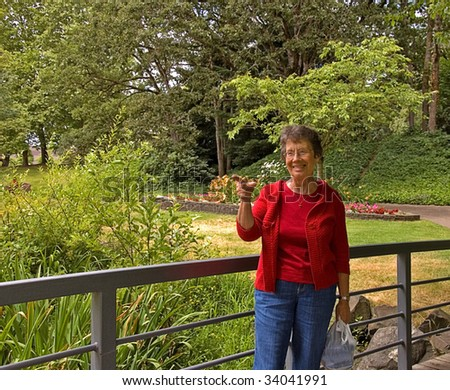 This elderly woman is outdoors in a park on a bridge and pointing her finger with a smile on her face in a captivating look.