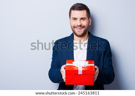 This gift is for you. Handsome young man in formalwear giving a gift to you while standing against grey background
