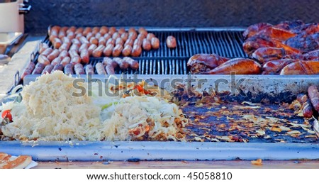 This grill scene is hotdogs, sausages, sauerkraut, BBQ chicken sizzling hot on an outdoor grill.