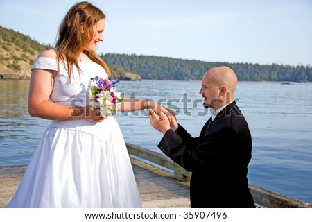 This groom is on his knees putting the ring on his young bride's finger on a dock in a beautiful ocean setting. - stock photo