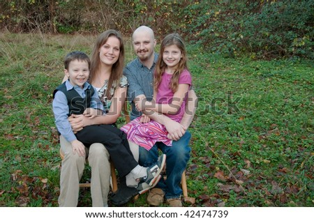 This happy Caucasian family is smiling outdoors in a portrait setting, mom, dad, brother and sister.  Background is intentionally blurred for artist effect.