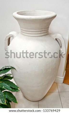 This home related object is a very large, white pottery vase in an interior setting.