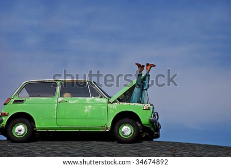 This humorous photo depicts a woman's mannequin legs sticking out of the hood of a small green car's hood against bright blue sky.