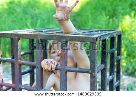 Photo of This image calls for the protection of human rights and the fight against violence. the child reaches up, asks for help, wants to be free. 5 years old boy sits in a cell
