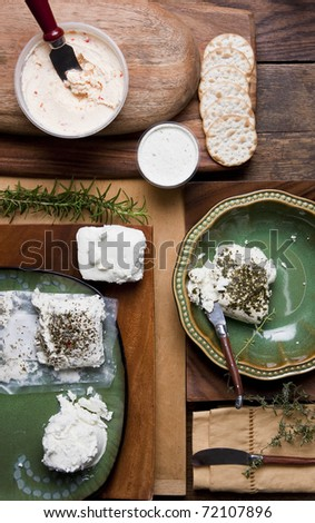 This image contains a very natural setting of organic cheese in a picnic style shot from overhead. There's lots of natural wood, organic tones.