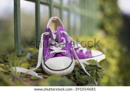 This image expresses the freedom and carefree children; concepts represented from the outdoors where the photo was taken and the string untied. / outdoor portrait of a little girl sneakers shoes #391054681