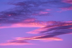 This image features an idyllic calm sky filled with pink and purple clouds illuminated by a stunning sunset.