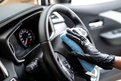 This image is a picture of wiping the car by a blue microfiber cloth with hand wearing gloves.Car wash concept.