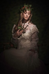 This image is a stylized painterly portrait of young woman in fancy white lace antique dress with a holly crown on , loving holding an old brass statue and looking downwards.