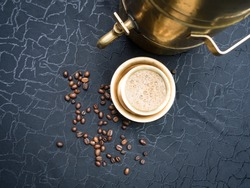 This image is about a top view of a traditional South Indian coffee from Bangalore. Made with fresh roasted coffee beans served in a golden cup. With a black background