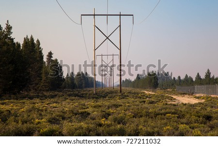 this image of powerlines in the country with blue sky and green grass surrounding it is a beautiful landscape that pumps electricity from one industry to another through steel cables and voltage #727211032