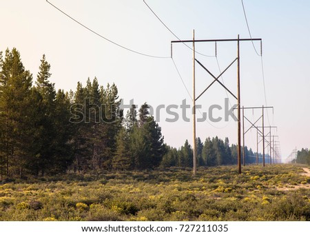 this image of powerlines in the country with blue sky and green grass surrounding it is a beautiful landscape that pumps electricity from one industry to another through steel cables and voltage #727211035
