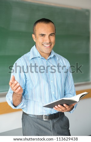 This image shows a Hispanic Male Teacher in his classroom - stock photo