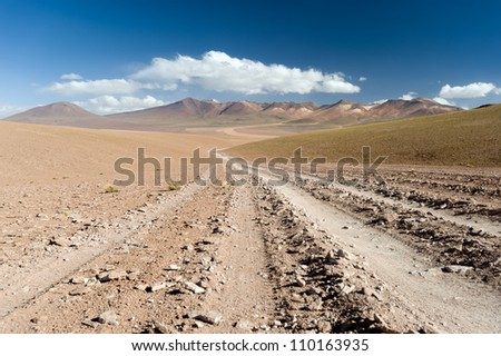 THis image shows a road leading into the colourful high Andean landscape.