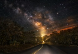 This image shows an epic night time milky way sky over a remote, secluded road.