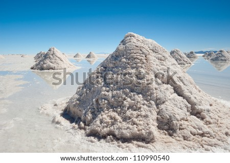 This image shows salt piles on Bolivia's Salar De Uyuni - stock photo