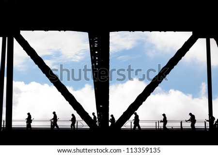 This image shows silhouetted People on the Harbour Bridge, Sydney Australia - stock photo