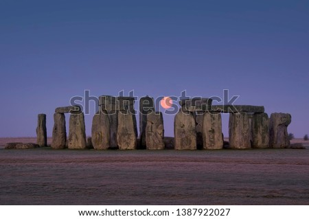 This image shows the ancient stones of Stonehenge with glowing moon between megaliths, Wiltshire, England Stock photo ©