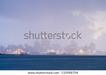 This image shows the Auckland skyline in a raincloud , New Zealand