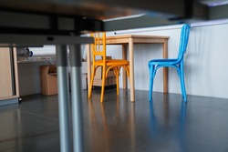 This image shows two chairs in color and a brown table. The chairs are blue and yellow. The view angle is unkommon form underneath.