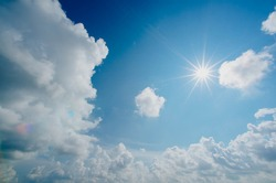 This is a beautiful bright day in which a sunshine in cumulus clouds and blue sky.  Sun is a source of light and heat and the clouds are source of rain. white Clouds attract the humans.
