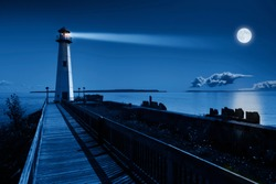 This is a beautiful photo illustration of a dramatic night time scene with a large blue moonrise in a clear sky on a ocean pier with a brightly lit lighthouse beacon and calm ocean waters.